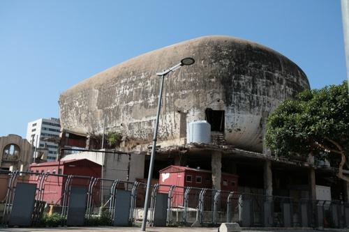 Sur la place des Canons, à proximité un reste de la guerre, l'immense salle de cinéma inaugurée quelques semaines avant la guerre qui n'a pas été reconstruit depuis.