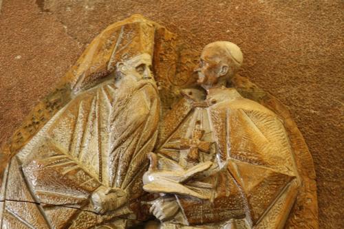 Cette sculpture doit représenter la rencontre historique entre le pape Paul VI et le Patriarche Athénagoras à Jérusalem en janvier 1964. Ce fut la première rencontre depuis plusieurs siècles entre  Rome et Constantinople, l'Eglise catholique et l'Eglise orthodoxe.
