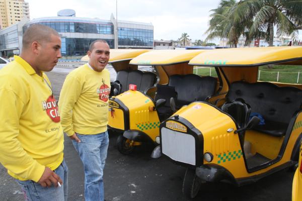 En Jaune, il y a les cocotaxis et leurs chauffeurs à La Havane près de l'Hôtel Rivierra.