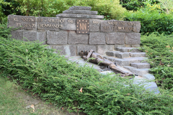 Ce monument en pierre d'Alsace rappelle la forme du triangle porté par les déportés sur leur tenue. Cet ensemble est dédié aux déportés politiques (triangle rouge) et plus particulièrement aux déportés NN (Nacht unt Nebel) nombreux au camp du Struthof. La sculpture en bronze est une réplique de celle de Georges Halbour (Le Gisant) que l'on peut voir sur à l'entrée du camp sur le site du Struthof.